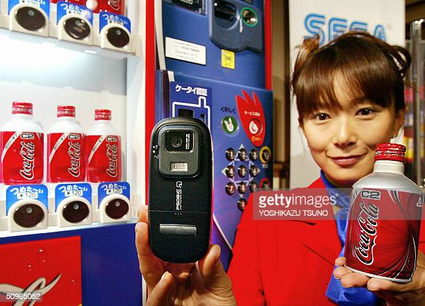 An employee for CocaCola Japan demonstrates how to buy a soft drink from a vending machine with NTT DoCoMo's mobile phone equipped with Sony's...