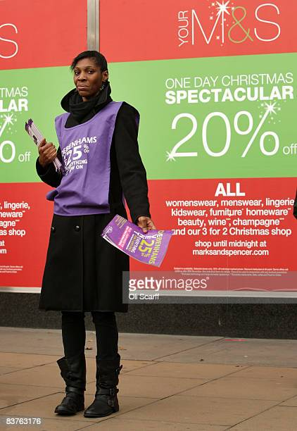 An employee for Debenhams hands out flyers advertising a 25% off sale outside their principle rival the Marks and Spencer department store on Oxford...