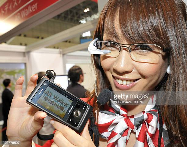 An employee for Japanese mobile communication company NTT docomo wears a headmounted display to demonstrate their augmented reality application...