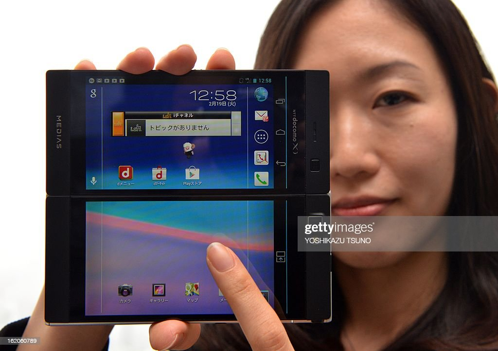 An employee for Japan's NEC Casio Mobile displays a dual-screen folding smartphone called 'Medius W N-05E', which has two 4.3-inch LCD displays and that combined for a 5.6-inch sized square screen, at NEC headquarters in Tokyo on February 19, 2013. The Android 4.1 smartphone allows users to use both screens together or the second screen for a different task such as screen-keyboard. NEC Casio Mobile will ship it for Japanese mobile carrier NTT docomo from April. AFP PHOTO / Yoshikazu TSUNO