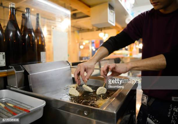 An employee fries Kushikatsu at a Kushikatsu Tanaka restaurant operated by Kushikatsu Tanaka Co in Tokyo Japan on Thursday April 20 2017 Kushikatsu...