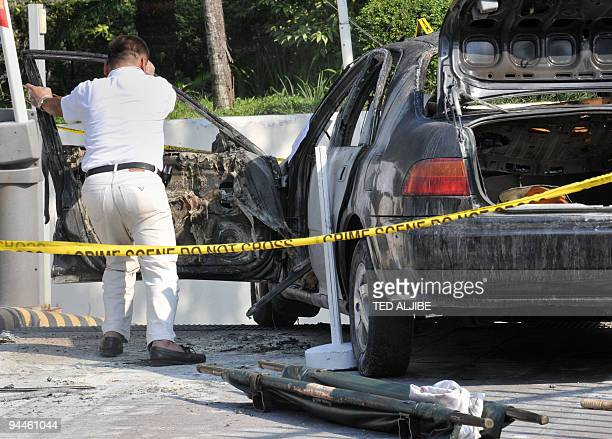 An employee from a funeral parlor opens the door of a car to remove the victim after a blast inside the vehicle in the upscale district of Taguig in...