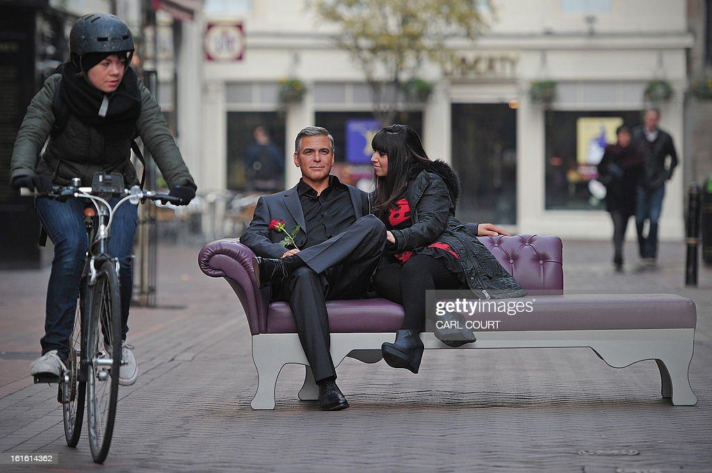 An employee (R) from London's Madame Tussauds poses for pictures with a waxwork model of US actor George Clooney during a photocall to mark Valentines Day in central London, on February 13, 2013.