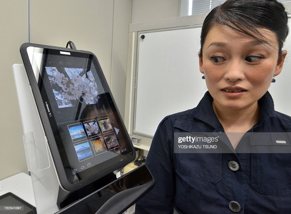 An employee from NTT DoCoMo demonstrates the prototype model of a new hands-free tablet operated by eye-controled input with an infrared eye-tracking device at a press preview in Tokyo on September 19, 2012. The user can scroll a browser, turn pages of electronic books and play games. AFP PHOTO / Yoshikazu TSUNO