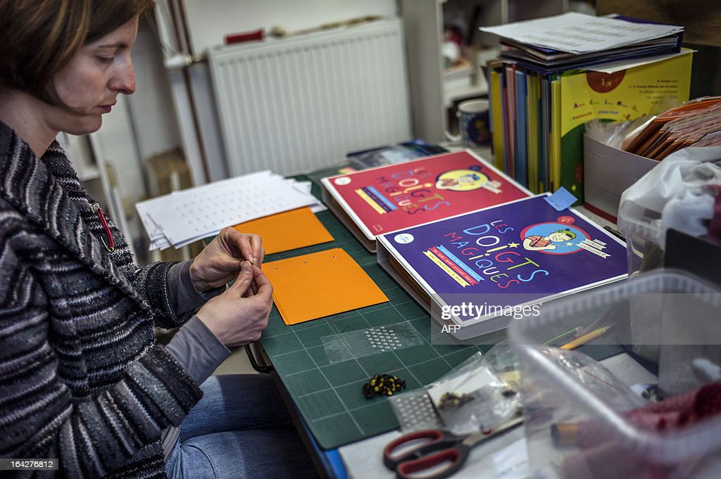 An employee from the publishing house, 'Les doigts qui revent' (Fingers who dream) works at the design of tactile books for blind children, in Talant, centraleastern France, on March 20, 2013. The publisher will participate in the Paris yearly book fair scheduled from March 22 to March 25, 2013.