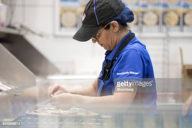 An employee garnishes a pizza base with toppings inside a Domino's Pizza Group Plc store in Hanwell London UK on Monday Feb 27 2017 Domino's Pizza...