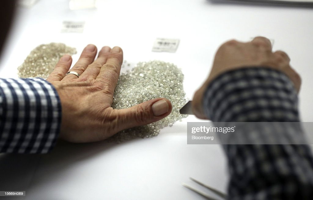 An employee gathers a pile of uncut diamonds ready for grading in this arranged photograph at the De Beers office in London, U.K., on Friday, Nov. 16, 2012. De Beers, the biggest diamond producer by revenue, is moving the sorting and trading of rough stones to Botswana from London to secure access to the world's largest supplier of diamonds by value and challenge Antwerp's dominance as the world's biggest trading hub for rough diamonds. Photographer: Chris Ratcliffe/Bloomberg via Getty Images