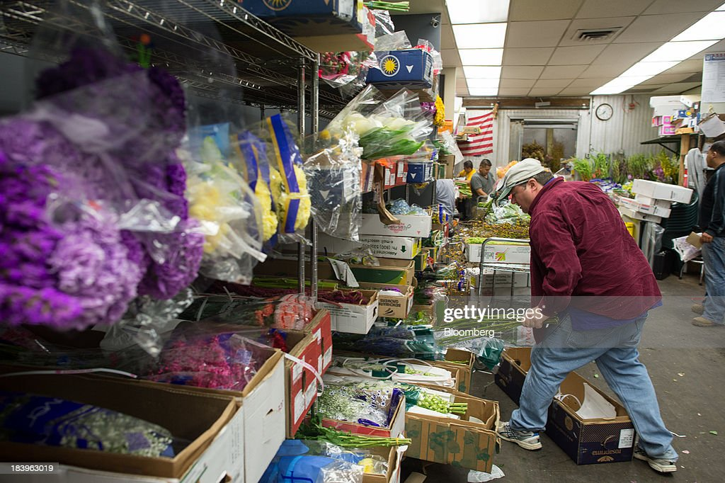 An employee gathers flowers for orders at George Rallis Inc. wholesale flower shop in New York, U.S., on Monday, Oct. 7, 2013. Wholesale inventories figures, which were scheduled for Oct. 9 by the U.S. Census Bureau, will not be released due to the partial government shutdown. Photographer: Craig Warga/Bloomberg via Getty Images