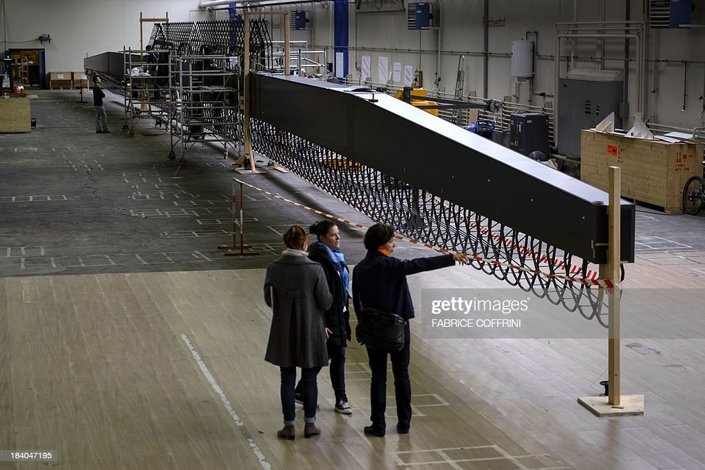 An employee gestures next to the carbon-fibre 72 metres long wing of Swiss sun-powered aircraft Solar Impulse HB-SIB on October 11, 2013 in construction at the former military airport of Duebendorf, near Zurich. After this years flight across United States with Solar Impulse HB-SIA prototype aircraft, a new larger plane is being built and expected to fly around the world in 2015.