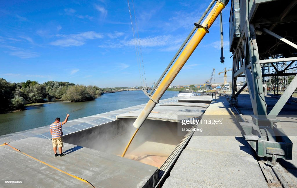 An employee gives a signal during the loading of corn grain into the hold of the Dutch cargo ship Amice II at Granexport AD port, part of MK Group, on the Danube river in Pancevo, Serbia, on Tuesday, Oct. 9, 2012. Goods volumes on Europe's longest river after the Volga are 80 percent lower than on the Rhine, the region's busiest waterway, according to EU figures. Photographer: Oliver Bunic/Bloomberg via Getty Images