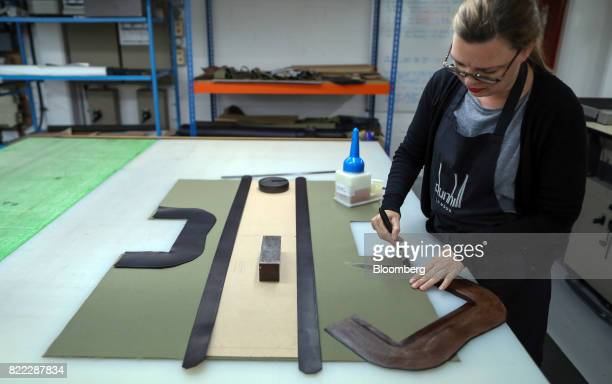 An employee glues a section of canvas on a Kempton canvas tote bag at the Alfred Dunhill Ltd London Leather Workshop in London UK on Tuesday July 25...