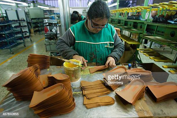 An employee glues insoles for shoes at the Always Shoes SA factory in Felgueiras Portugal on Wednesday Dec 18 2013 Portugal's Prime Minister Pedro...