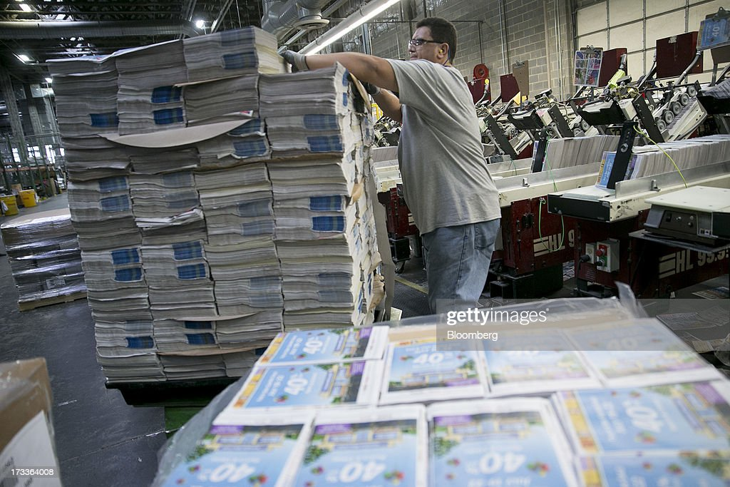 An employee grabs advertisement insets to feed into a collator machine at the Washington Post newspaper production facility in Springfield, Virginia, U.S., on Friday, July 12, 2013. The Washington Post began publishing on Thursday, Dec. 6, 1877, and had a circulation of 10,000. The newspaper contained four pages and cost three cents a copy. Photographer: Andrew Harrer/Bloomberg via Getty Images