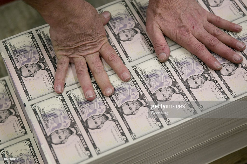 An employee grabs sheets of five dollar to be loaded into a machine at the Bureau of Engraving and Printing in Washington, D.C., U.S., on Tuesday, April 23, 2013. Stocks rallied amid growth in U.S. home sales, better-than-forecast earnings and speculation the European Central Bank will cut interest rates. U.S. equities recovered after briefly erasing gains following a false report of explosions at the White House. Photographer: Andrew Harrer/Bloomberg via Getty Images