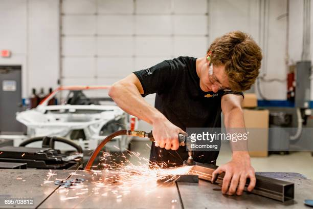 An employee grinds frame rail connectors while working on the chassis of a General Motors Co Chevrolet COPO Camaro performance vehicle at the...