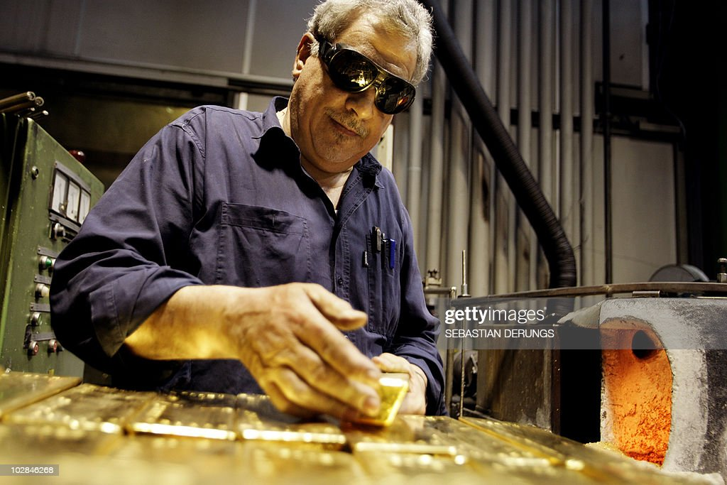 An employee handles a 125 kilo gold bar on April 6 2009 at a plant of gold refiner and producer ArgorHeraeus in Mendrisio in the southern Swiss...