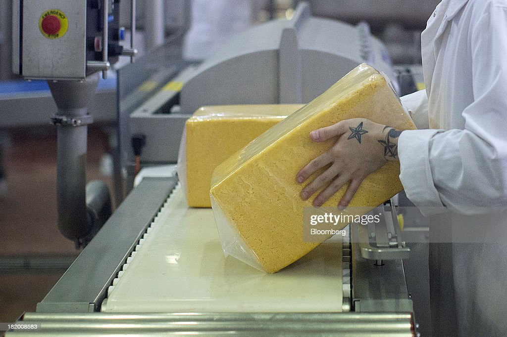 An employee handles a block of Red Leicester cheese as it moves along the packaging line at Wyke Farms Ltd., in Bruton, U.K., on Friday, Sept. 27, 2013. Wyke Farms, the U.K.'s largest family-owned cheese maker and milk processor, has started using waste from its cows and pigs to generate clean power and help shave as much as 1 million pounds ($1.6 million) a year off its energy bills. Photographer: Simon Dawson/Bloomberg via Getty Images