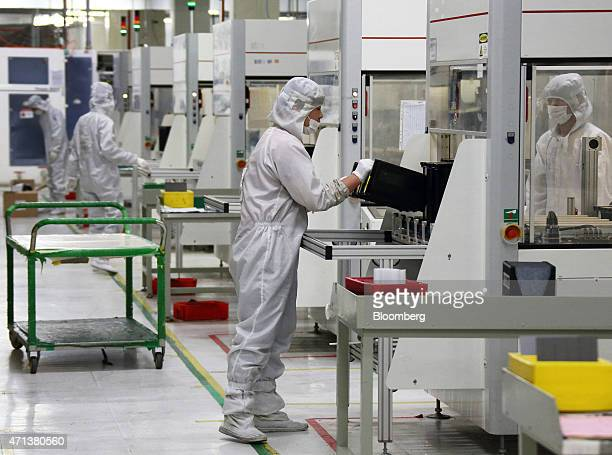 An employee handles a holder for solar cells on the production line at the Trina Solar Ltd factory in Changzhou Jiangsu Province China on Friday...