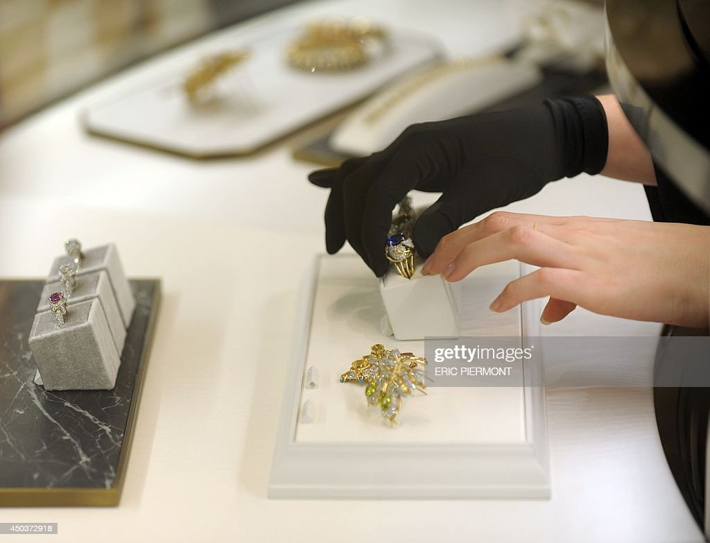An employee handles a jewel ring at the Tiffany and Co jewellery store on on the Champs Elysees on June 10 on the day of the opening of the luxury...