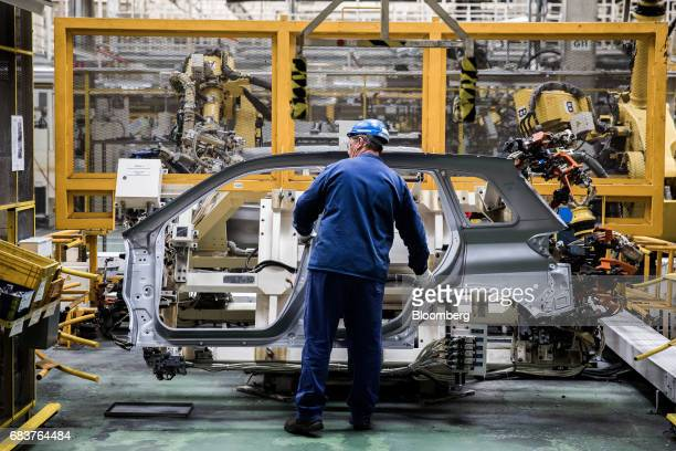 An employee handles an automobile body frame panel on the production line inside the Suzuki Motor Corp plant in Esztergom Hungary on Monday May 15...