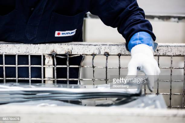 An employee handles automobile panels on the production line inside the Suzuki Motor Corp plant in Esztergom Hungary on Monday May 15 2017 European...