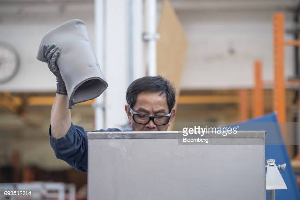 An employee handles clay to be shaped into tile pieces at the Heath Ceramics Ltd production facility in San Francisco California US on Friday June 2...