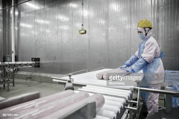 An employee handles imported Smithfield Foods Inc pork meat on a production like that processes the pork into ham at the WH Group Ltd facility in...