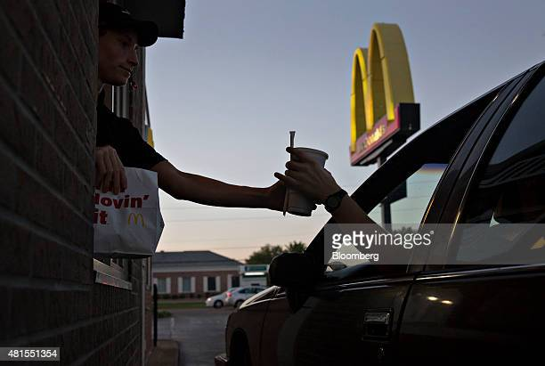 An employee hands a beverage to a customer at the drivethru window of a McDonald's Corp restaurant in Peru Illinois US on Monday July 20 2015...