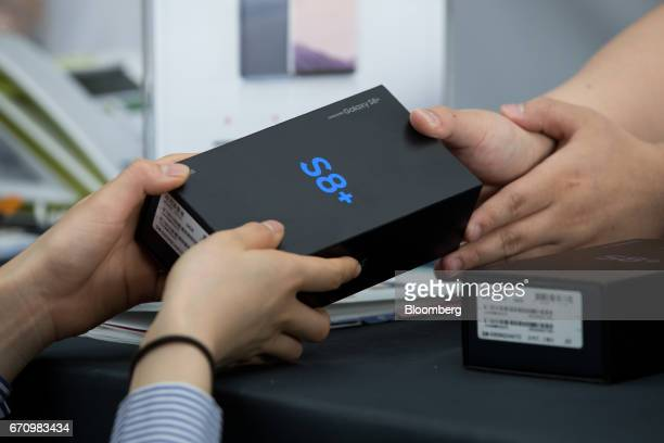 An employee hands a box containing a Samsung Electronics Co Galaxy S8 smartphone to a customer at KT Corp's Olleh Square flagship store in Seoul...