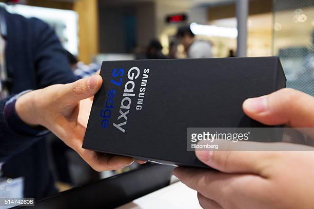 An employee hands a box of Samsung Electronics Co Galaxy S7 Edge smartphone to a customer at the company's D'light flagship store in Seoul South...