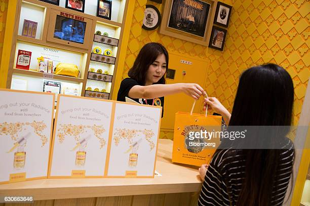 An employee hands a branded shopping bag to a customer at a Burt's Bees Inc store a subsidiary of Clorax Co in Seoul South Korea on Thursday July 2...