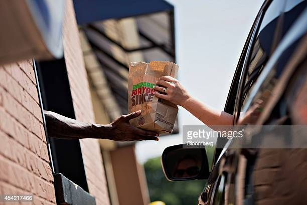 An employee hands a customer their order at the drivethrough of a Burger King Worldwide Inc restaurant in Peoria Illinois US on Tuesday Aug 26 2014...