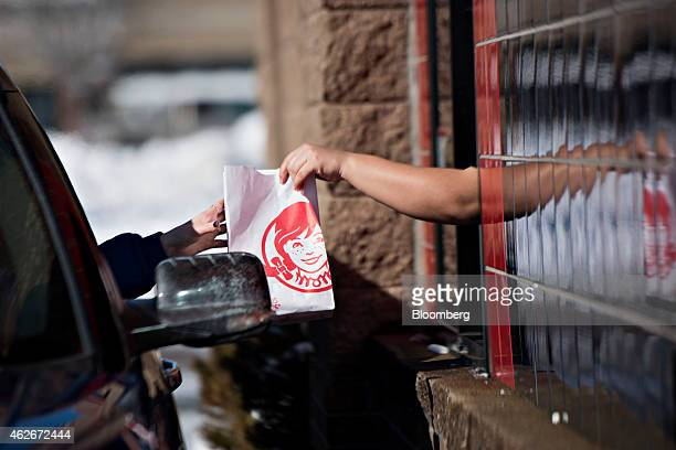 An employee hands a customer their order at the drivethru window of a Wendy's Co restaurant in Peoria Illinois US on Monday Feb 2 2015 Wendy's Co is...