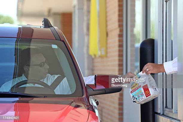 An employee hands a drivethru customer his food order a McDonald's Corp restaurant in Oak Brook Illinois US on Friday July 12 2013 Don Thompson...