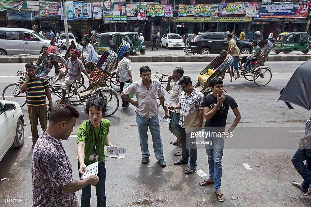 An employee hands a leaflet to a passing pedestrian at the opening of a Grameen Uniqlo store, a joint venture between Fast Retailing Co. and Grameen Healthcare Trust, in the Paltan area of Dhaka, Bangladesh, on Saturday, Oct. 5, 2013. Fast Retailing, Asia's biggest clothing retailer, set up the venture with Grameen Healthcare Trust to design, make and sell clothes in Bangladesh. Photographer: Jeff Holt/Bloomberg via Getty Images