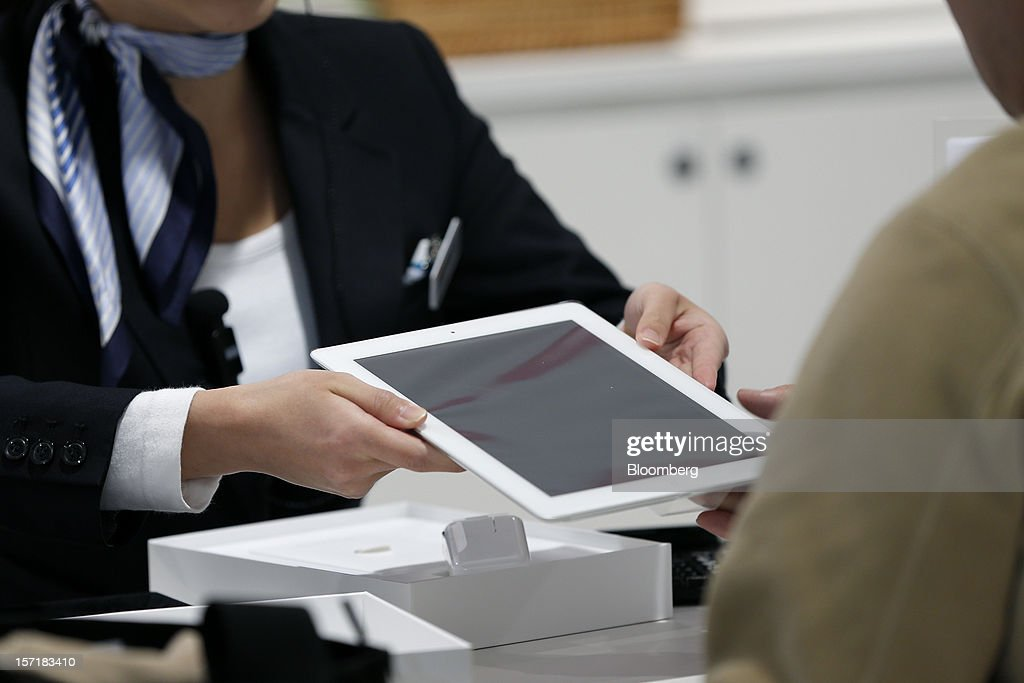 An employee hands a newly unboxed Apple Inc. iPad to a customer at a KDDI Corp. store in Tokyo, Japan, on Friday, Nov. 30, 2012. The iPad Mini went on sale at KDDI and Softbank Corp. stores in Japan today. Photographer: Kiyoshi Ota/Bloomberg via Getty Images
