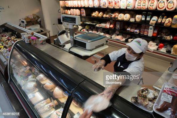 An employee hands a package of ham to a shopper at the delicatessen counter of a Superama grocery store in the La Condesa neighborhood of Mexico City...