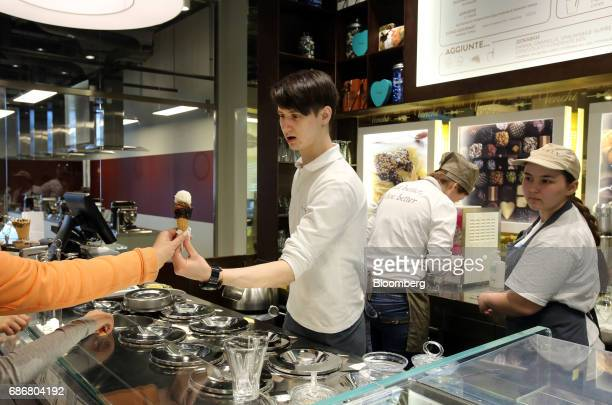An employee hands over a cornet of Italian 'gelato' ice cream inside the new Eataly food store operated by Eataly Net Srl at the Kievsky shopping...
