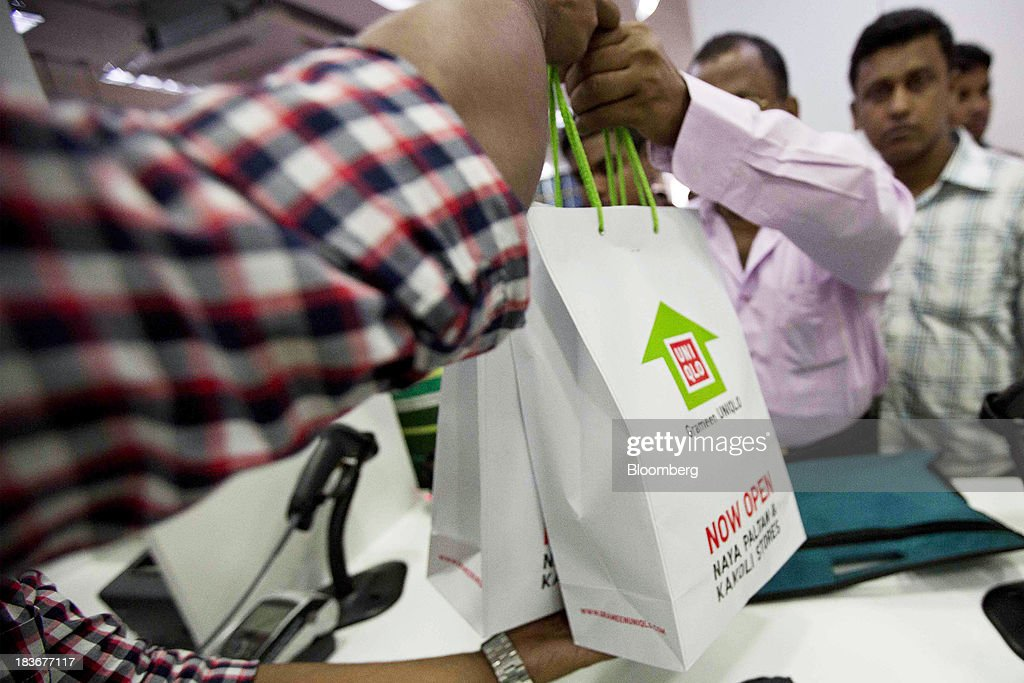 An employee hands over a shopping bag of clothing to a customer at the opening of a Grameen Uniqlo store, a joint venture between Fast Retailing Co. and Grameen Healthcare Trust, in the Paltan area of Dhaka, Bangladesh, on Saturday, Oct. 5, 2013. Fast Retailing, Asia's biggest clothing retailer, set up the venture with Grameen Healthcare Trust to design, make and sell clothes in Bangladesh. Photographer: Jeff Holt/Bloomberg via Getty Images