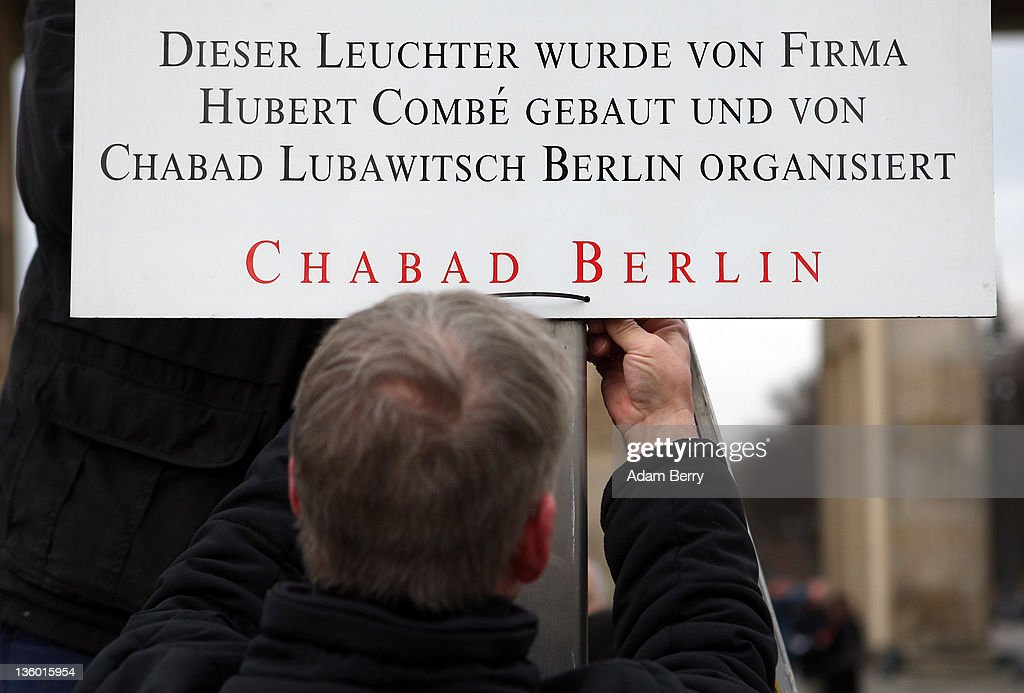 An employee hangs a sign crediting the company Hubert Combe and the Chabad Lubavitch community with erecting a large nine-armed candleholder, a Hannoukiah, or Menorah, ahead of the start of the eight-day-long and annual Jewish Festival of Lights known as Chanukah, in front of the Brandenburg Gate on December 20, 2011 in Berlin, Germany. The festival marks the rebellion of Maccabee Jews against the Greeks in 165 BC, which some believers say included a number of miracles pointing to divine providence.