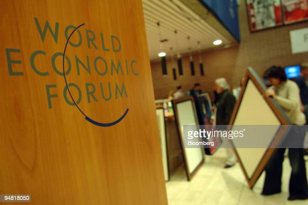 An employee hangs up paintings during preparation for the World Economic Forum in Davos Switzerland Monday January 23 2006 Is Warren Buffett going to...
