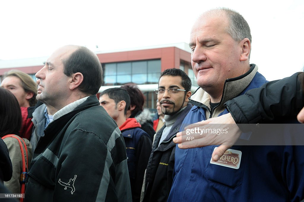 An employee has his jacket's Spanghero sign hidden by a co-worker as they gather for a statement to the press outside the headquarters of French meat supplier Spanghero in Castelnaudary, southwestern France, on February 15, 2013. The president of Spanghero, designated by the French government as the main person responsible in the horse meat scandal, pleaded good faith today and characterised France's Consumer Affairs Minister as 'extremely imprudent' in his announcements the day before. The French government said the French firm Spanghero knowingly sold horsemeat as beef and that it was withdrawing the licence that allowed it to process meat.