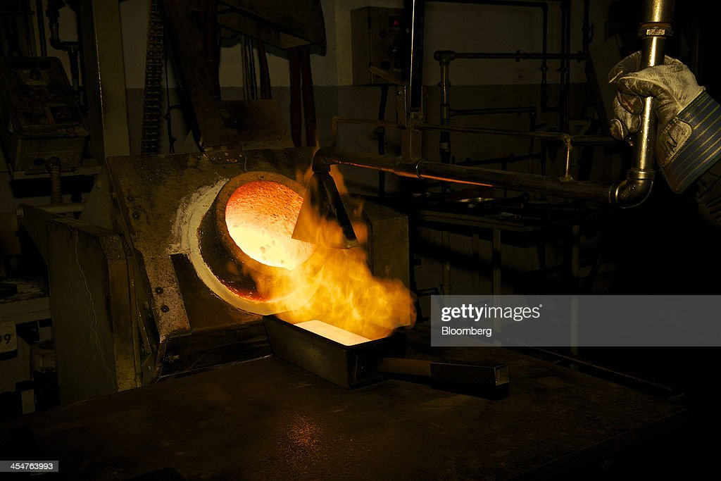 An employee heats a freshly cast 400 ounce gold bar during the semiautomated gold bar manufacturing process at a precious metal refinery near...