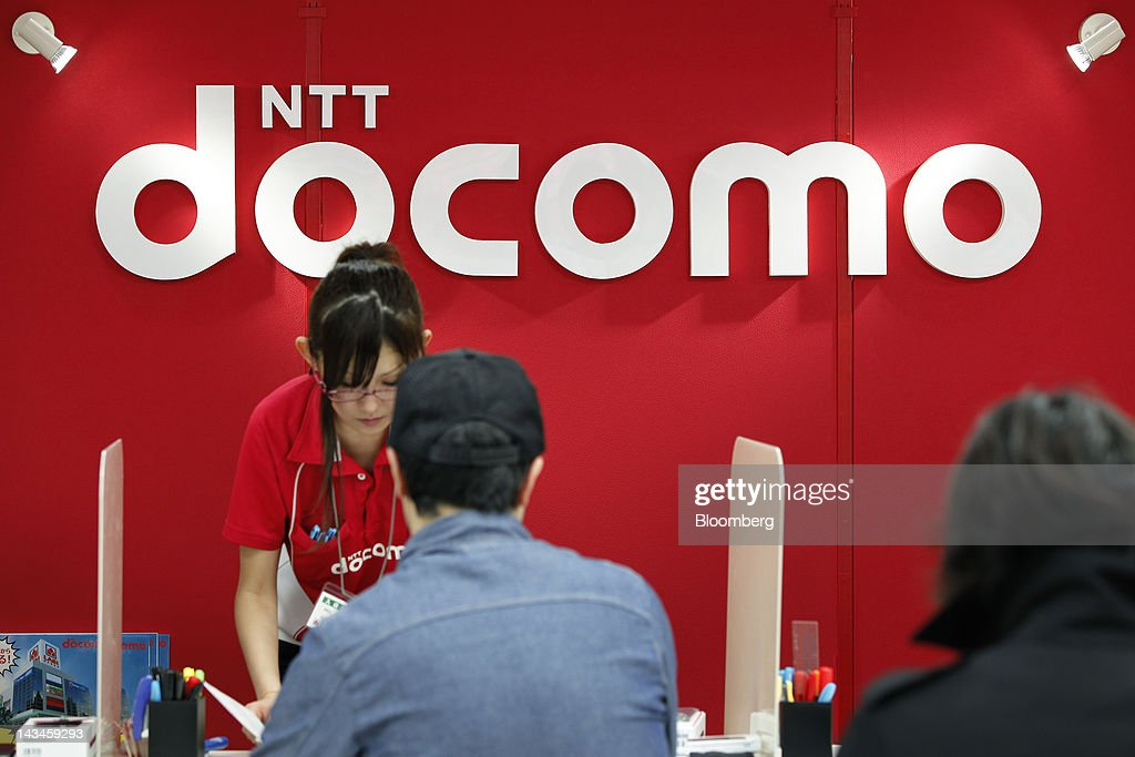 An employee helps a customer at a counter for NTT DoCoMo Inc. at the Labi Ofuna electronics store, operated by Yamada Denki Co., in Yokohama City, Kanagawa Prefecture, Japan, on Friday, April 27, 2012. Consumer prices excluding fresh food rose 0.2 percent from the year before, exceeding estimates, a government report showed earlier today. Photographer: Kiyoshi Ota/Bloomberg via Getty Images