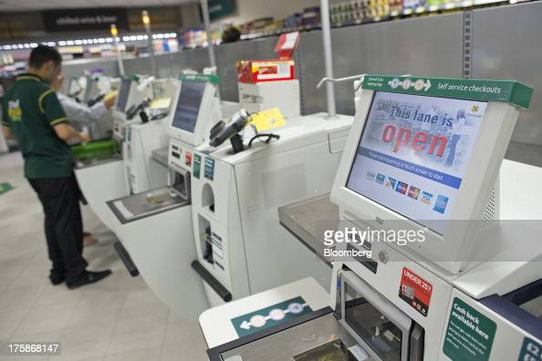 An employee helps a customer pay for their purchases at the selfservice checkout counters inside a Morrisons M Local store operated by William...