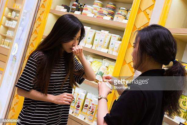 An employee helps a customer try on a product sample at a Burt's Bees Inc store a subsidiary of Clorax Co in Seoul South Korea on Thursday July 2...