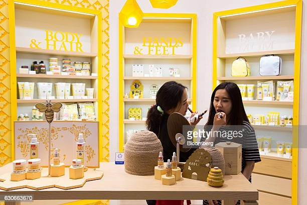 An employee helps a customer try on lip color at a Burt's Bees Inc store a subsidiary of Clorax Co in Seoul South Korea on Thursday July 2 2015 At a...