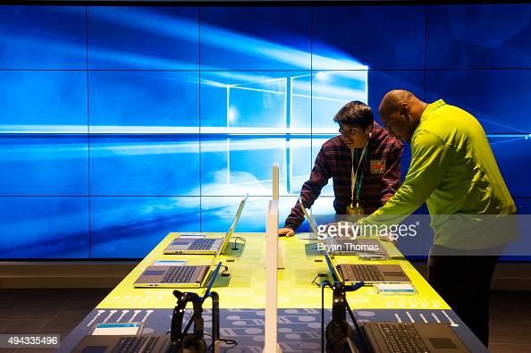 An employee helps a customer use a Dell computer at Microsoft's first flagship store on Fifth Avenue on October 26 2015 in New York City Hundreds of...