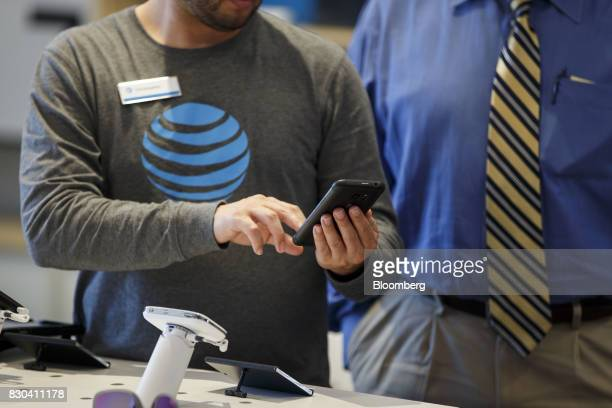 An employee helps a customer with a smartphone at an ATT Inc store in Newport Beach California US on Thursday Aug 10 2017 ATT Inc shares surged the...