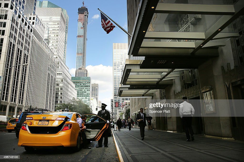 An employee helps a guest outside of the Waldorf Astoria the landmark New York hotel is viewed on October 6 2014 in New York City It was announced...